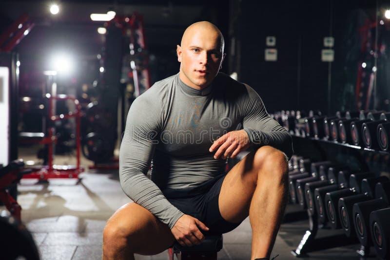 Den muskulösa mannen i en grå t-skjorta vilar mellan övningar i idrottshallen Idrottsman nen i konditionrummet royaltyfri bild