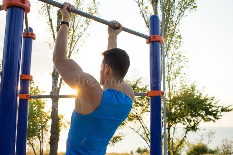 Den muskulösa mannen som gör handtag-UPS på horisontalstången, utbildning av strongmanen på utomhus-, parkerar idrottshall i morg royaltyfri foto