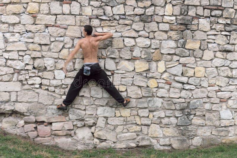 Den muskulösa passformen som är topless av man, utbildar stads- klättring arkivfoton