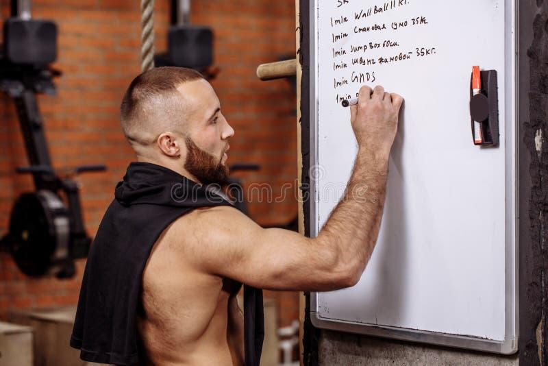 Den muskulösa passformgrabben skriver hans ett utbildningsprogram på brädet royaltyfri foto