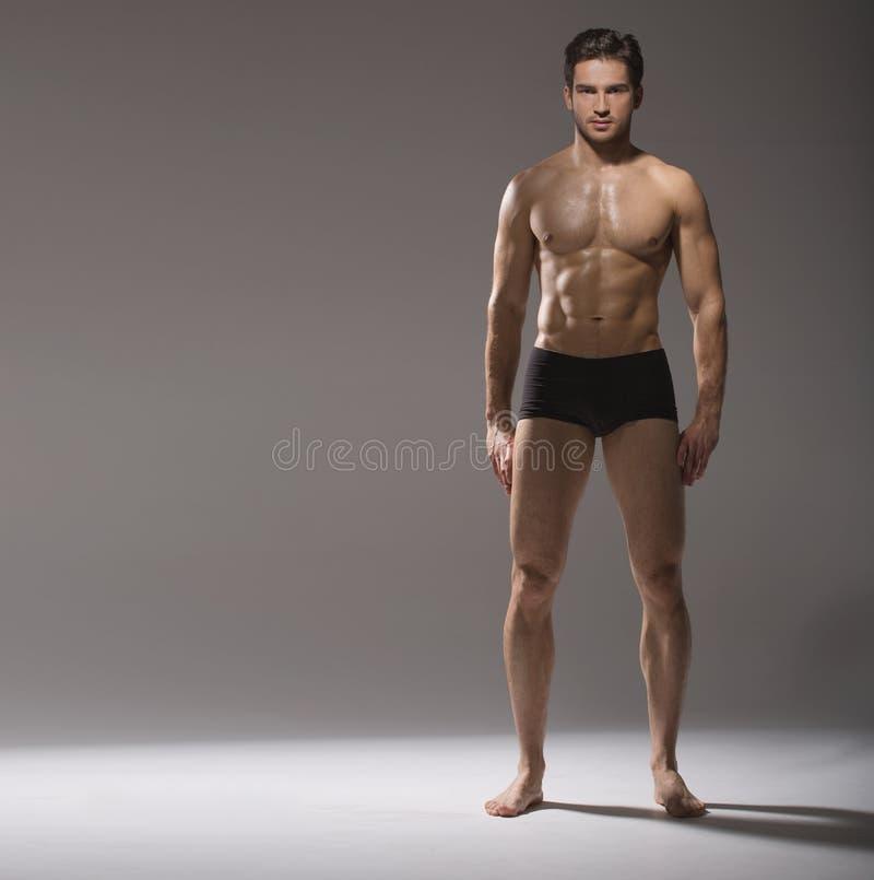 Den muskulösa stiliga grabben i stillhet poserar fotografering för bildbyråer