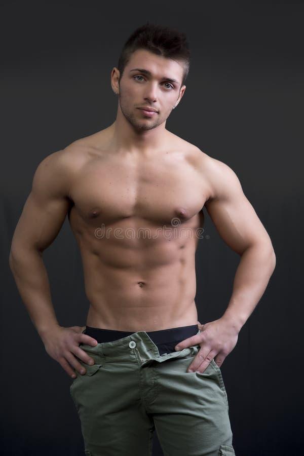 Den muskulösa unga mannen som är shirtless i avkopplat, poserar royaltyfria bilder