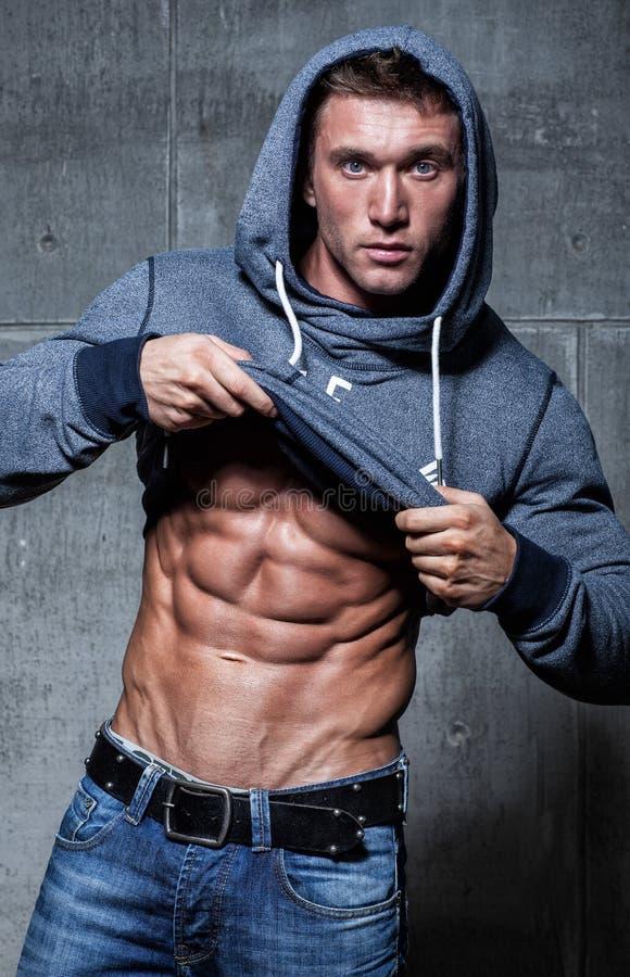 Den muskulösa unga sexiga mannen tar av hans kläder royaltyfri foto