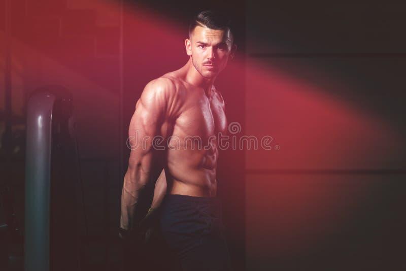 Den muskul?sa mannen som b?jer muskelsidotriceps, poserar royaltyfri bild