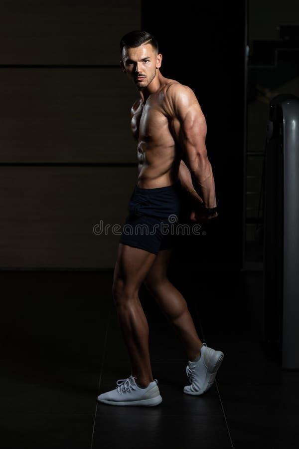 Den muskul?sa mannen som b?jer muskelsidotriceps, poserar arkivbilder