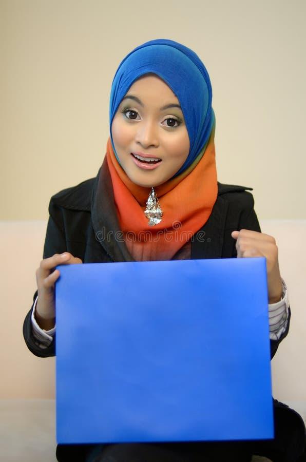 Den Muslimah affärskvinnan i den head halsduken med blått stiger ombord arkivfoto