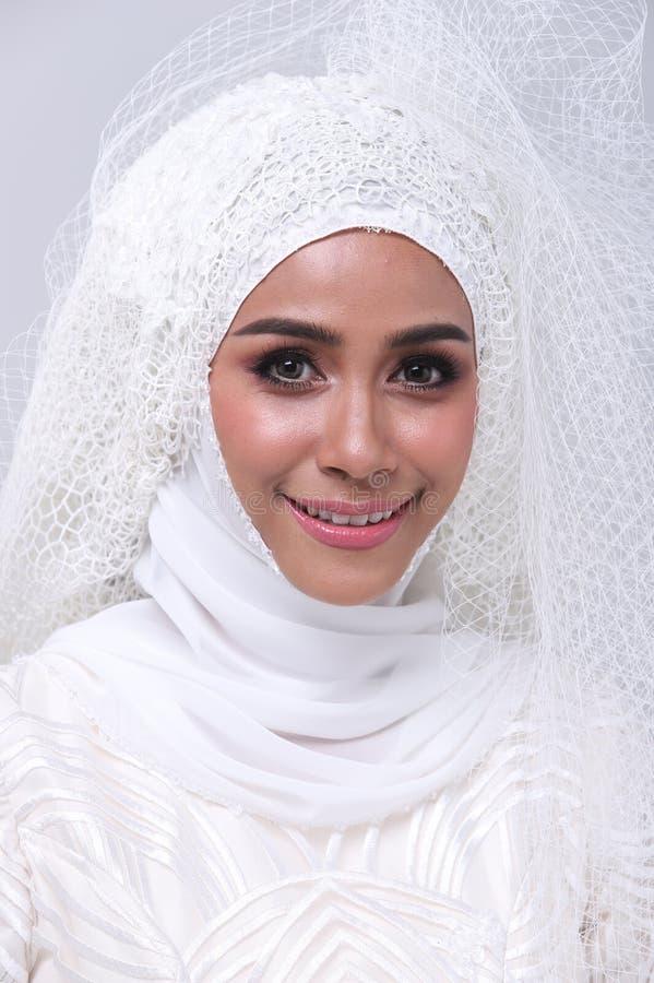 Den muslimska arabiska bruden snör åt in pärlbröllopsklänningen arkivbilder