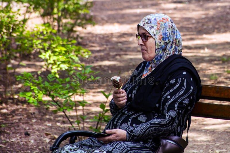 Den muslimska gamla kvinnan på bänk som kopplar av och, äter is proppar arkivfoton