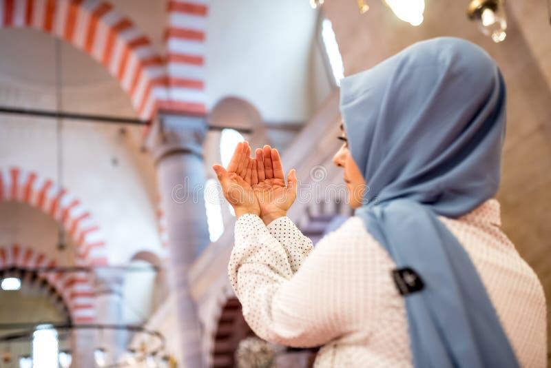 Den muslimska kvinnan i sjalett och en hijab ber arkivfoto