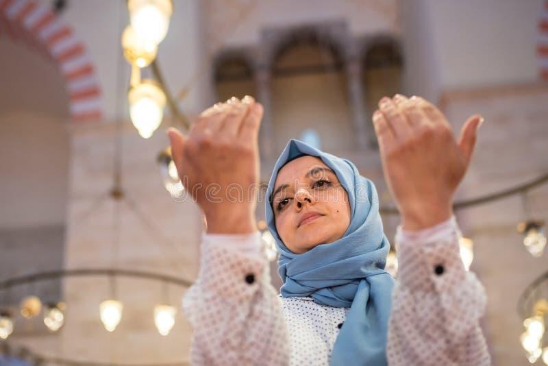 Den muslimska kvinnan i sjalett och en hijab ber arkivbilder