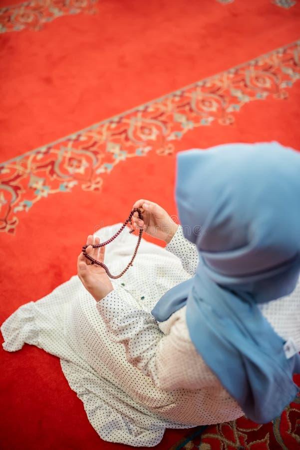 Den muslimska kvinnan i sjalett och en hijab ber royaltyfri foto