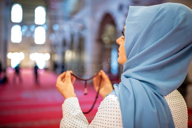 Den muslimska kvinnan i sjalett och en hijab ber fotografering för bildbyråer
