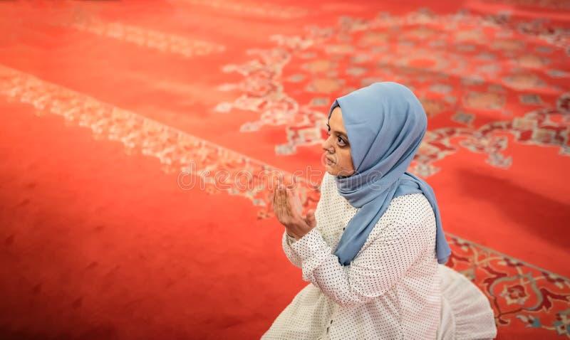 Den muslimska kvinnan i sjalett och en hijab ber royaltyfri bild