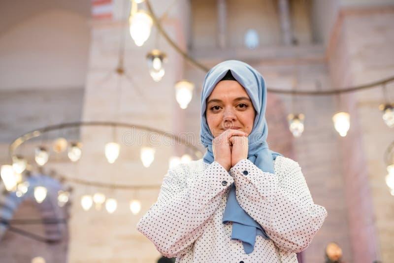 Den muslimska kvinnan i sjalett och en hijab ber arkivfoton