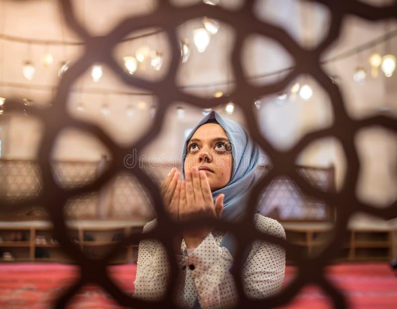 Den muslimska kvinnan i sjalett och en hijab ber royaltyfri fotografi