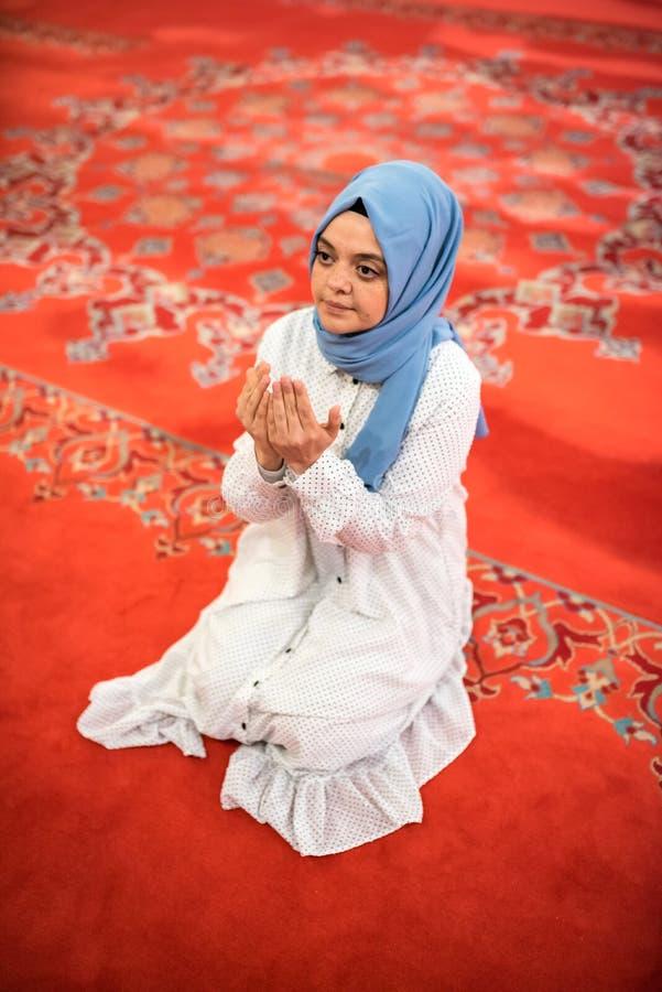 Den muslimska kvinnan i sjalett och hijab ber arkivfoto