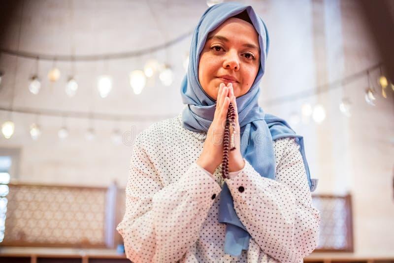 Den muslimska kvinnan i sjalett och hijab ber royaltyfria foton