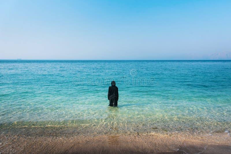 Den muslimska kvinnan p? stranden tillbaka besk?dar arkivfoto