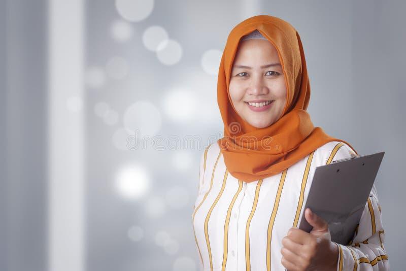 Den muslimska kvinnan rymmer skrivplattan arkivbild