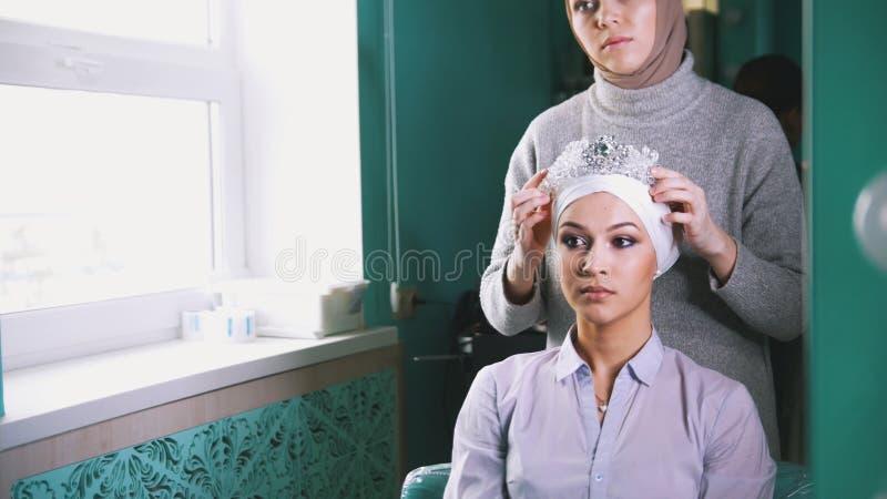 Den muslimska kvinnan sätter en tiara på det härliga huvudet för muslimbrud` s royaltyfria bilder