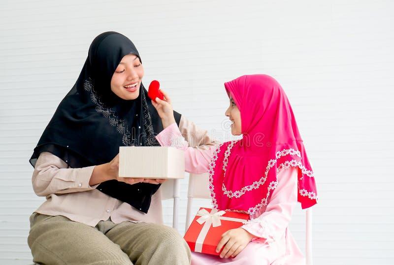 Den muslimska lilla flickan ger hjärtasymbol till hennes moder med begreppsförälskelse och förhållande i familj royaltyfria foton