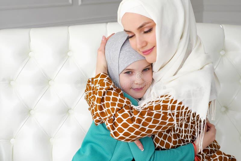 Den muslimska mamman och hennes lilla dotter i hijabs kramar att sitta p? soffan arkivfoto