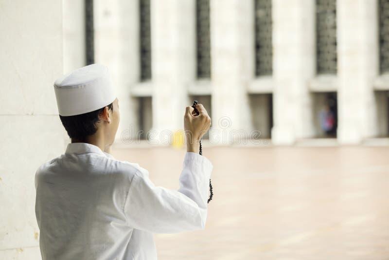 Den muslimska mannen ber till Allahen, når han har gjort Salat arkivbild