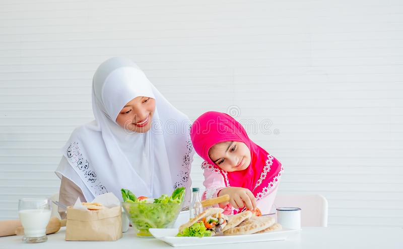 Den muslimska modern har handling för att motivera hennes dotter för att äta grönsaken, speciellt nya tomater för goda hälsor arkivbild