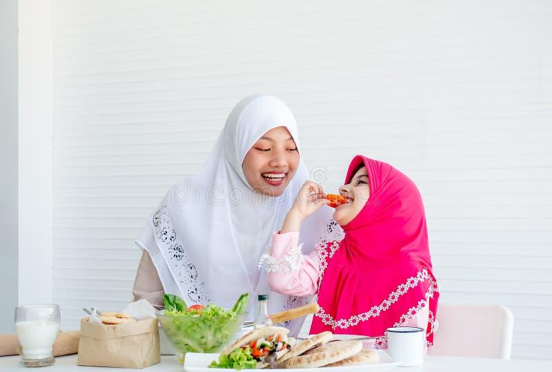 Den muslimska modern har handling för att motivera hennes dotter för att äta grönsaken, speciellt nya tomater för goda hälsor arkivfoton