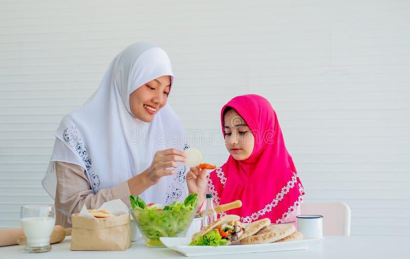Den muslimska modern har handling för att motivera hennes dotter för att äta grönsaken, speciellt nya tomater för goda hälsor royaltyfri bild