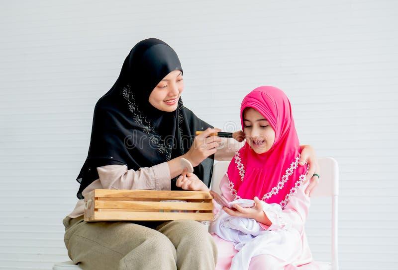 Den muslimska modern och hennes dotter är ålägger med kosmetisk aktivitet tillsammans i rummet med vitt bakgrunds- och kopierings fotografering för bildbyråer