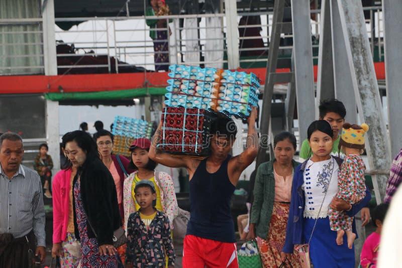 Den Myanmese arbetaren bär andägg i en spjällåda landsätter från skeppet med många passagerare går förbi bron av hamnen på arkivfoto
