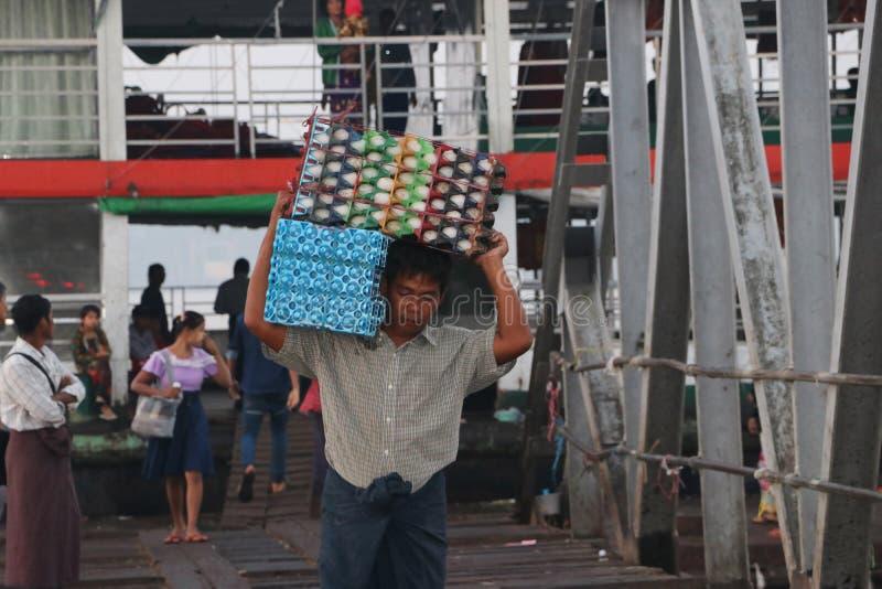 Den Myanmese arbetaren bär andägg i en spjällåda landsätter från skeppet och går förbi bron av hamnen på den Yangon floden royaltyfri foto