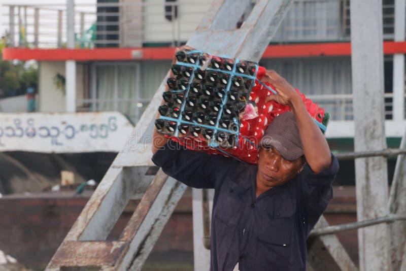 Den Myanmese arbetaren bär andägg i en spjällåda landsätter från skeppet och går förbi bron av hamnen på den Yangon floden royaltyfria foton