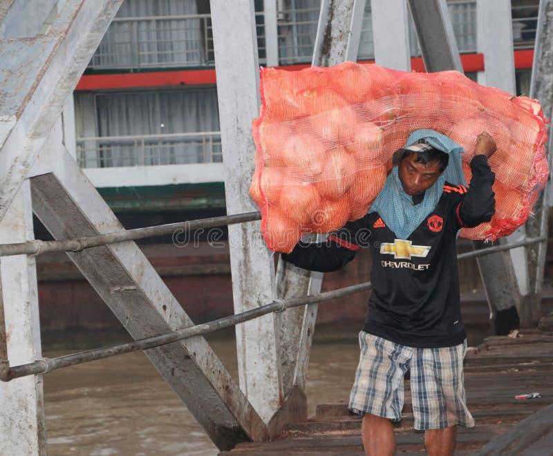 Den Myanmese arbetaren bär den stora påsekokosnöten landsätter från skeppet och går förbi bron av hamnen på den Yangon floden arkivfoton
