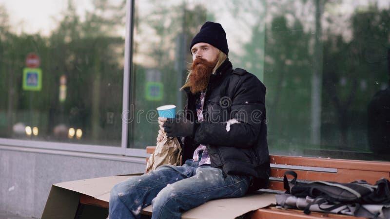 Den mycket berusade hemlösa mannen som talar till folk som går nära honom och, tigger för pengar, medan sitta på bänk på trottoar fotografering för bildbyråer
