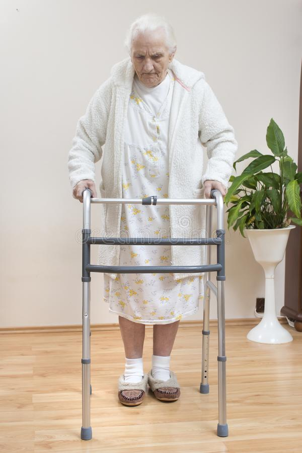 Den mycket gamla kvinnan i en vit badrock och nattlinne går med hjälpen av en rehabiliteringbalkong arkivbild