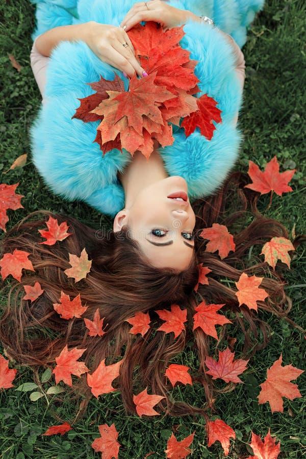 Den mycket härliga unga brunettkvinnan ligger på gräset, hennes orangutang royaltyfri bild