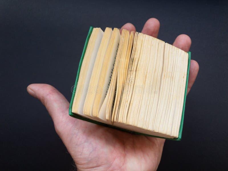 Den mycket lilla boken på människa gömma i handflatan arkivfoto