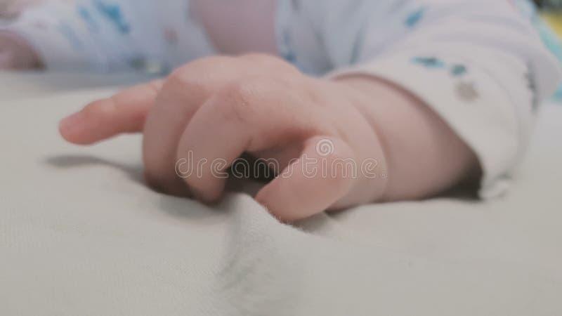 Den mycket lilla handen av ett litet behandla som ett barn att ligga på en säng och att nervöst skruva på sig royaltyfri bild
