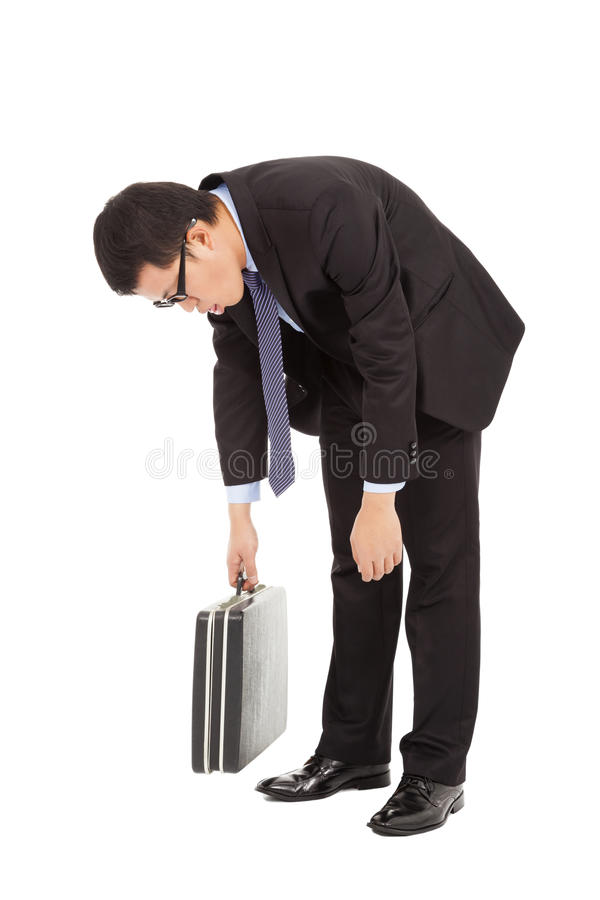 Den mycket trötta affärsmannen luta sig ner och rymma portföljen royaltyfri bild