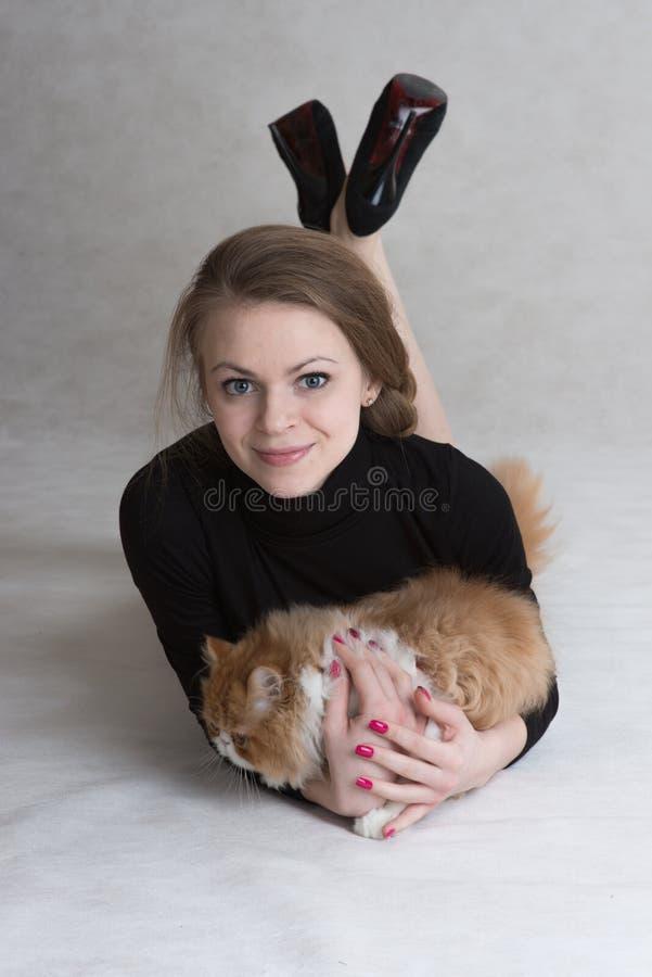 Den mycket trevliga flickan rymmer en röd kattunge royaltyfria foton