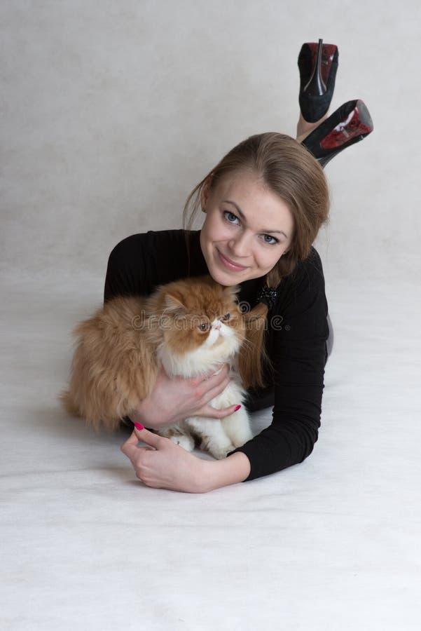 Den mycket trevliga flickan rymmer en röd kattunge arkivfoto