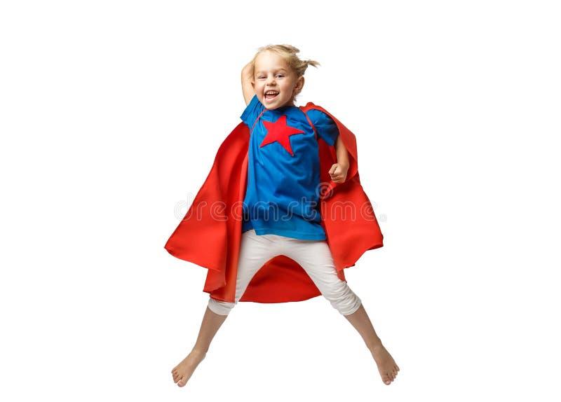 Den mycket upphetsade lilla flickan klädde som superherobanhoppning som isolerades på vit bakgrund royaltyfria bilder