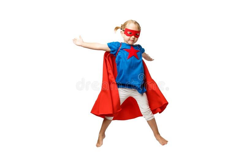 Den mycket upphetsade lilla flickan klädde som superherobanhoppning som isolerades på vit bakgrund arkivfoto