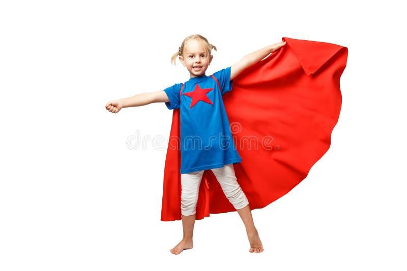 Den mycket upphetsade lilla flickan klädde som superherobanhoppning som isolerades på vit bakgrund arkivfoton