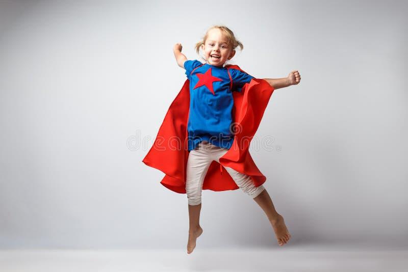Den mycket upphetsade lilla flickan klädde som superheroen som tillsammans med hoppar den vita väggen royaltyfri fotografi