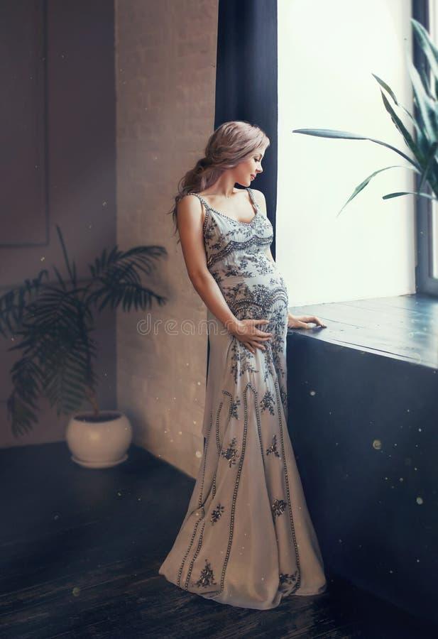 Den mystiska gravida drottningen, kvinnaställningar vid fönstret i vindrum, solljuset exponerar, samlat blont lockigt hår arkivbilder