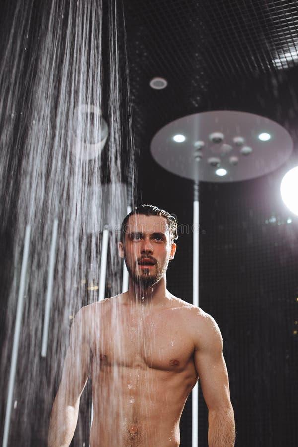 Den näcka brutala grabben ska ta en dusch kyla ner i dusch kallt huvud royaltyfri bild