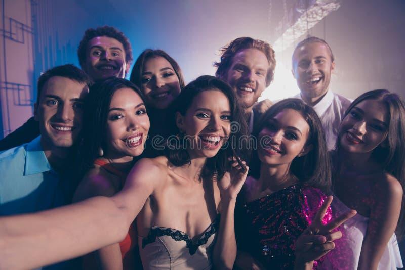 Den nära övre fotoståenden av vänner kelar till varandra och tar royaltyfri bild